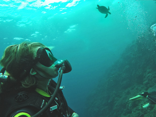 PIYOGA Founder Larissa Miller stares in awe of a beautiful sea turtle not too far away while diving in the ocean in Bali Indonesia