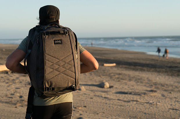 Guy walking on the beach with the paq bag