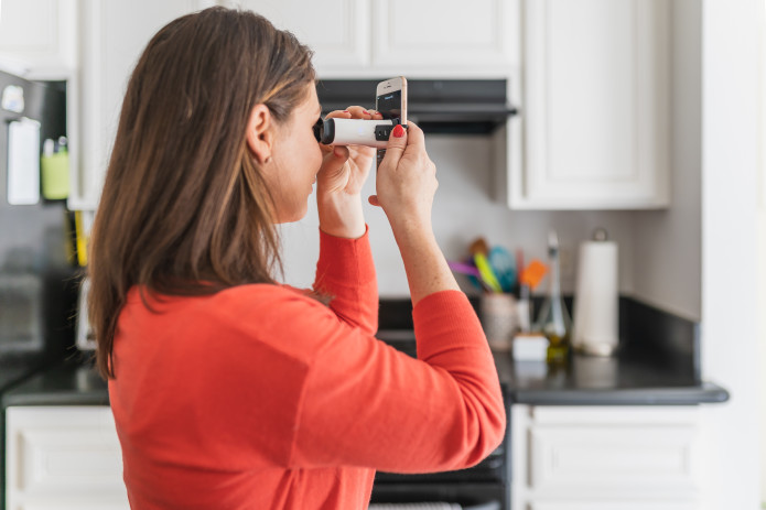 Woman testing her vision in her kitchen with the VisionCheck