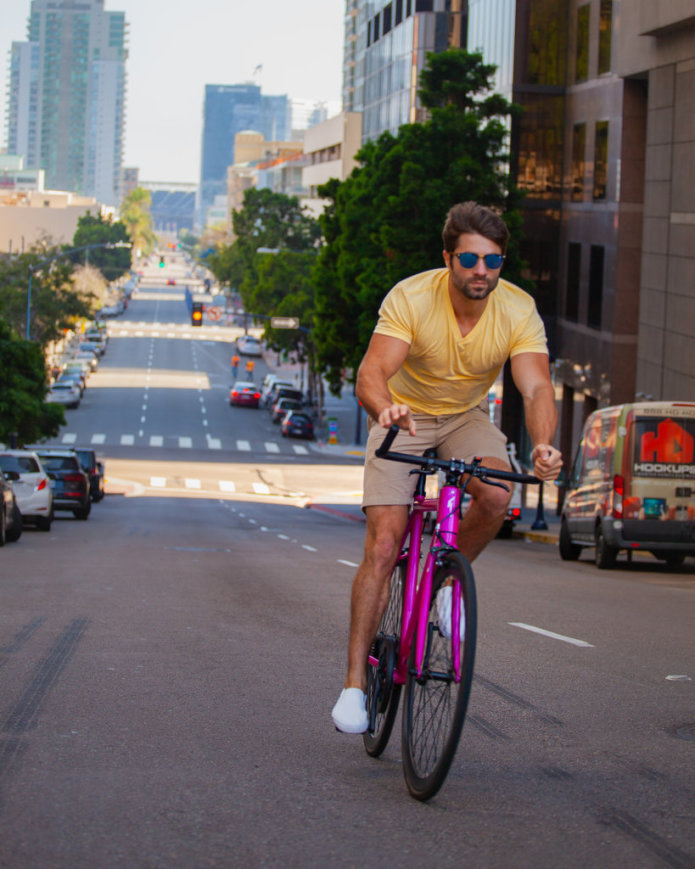 Rob Rast rides the FLX Babymaker Electric Road Bike up a steep hill in Downtown San Diego